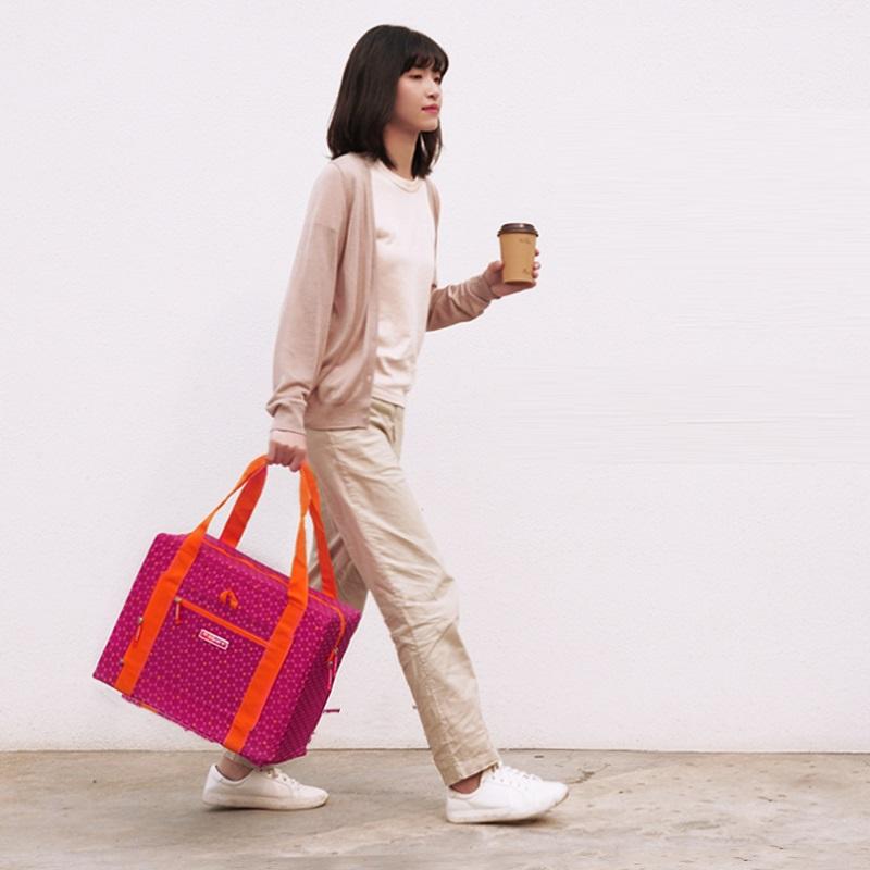 Cô gái đang xách túi đựng quần áo cỡ lớn Msquare Foldable màu hồng
