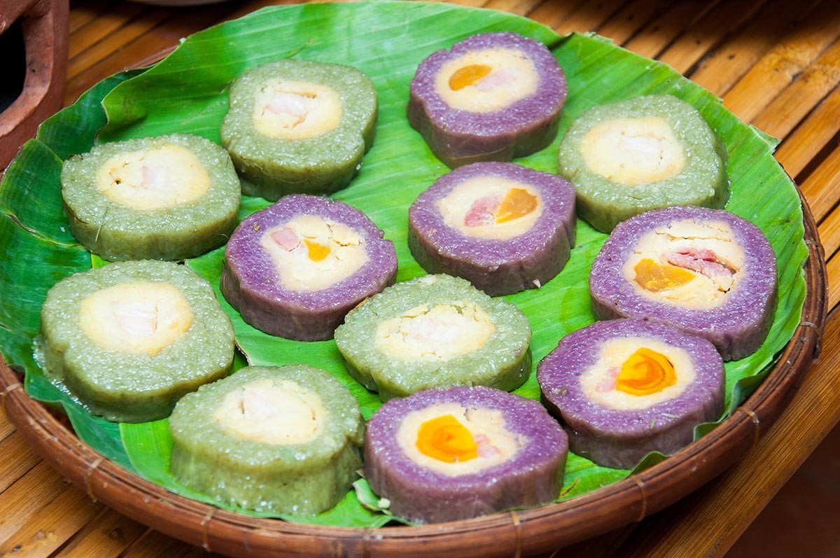 Những chiếc bánh tét lá cẩm màu tím trên chiếc mẹt lót lá chuối