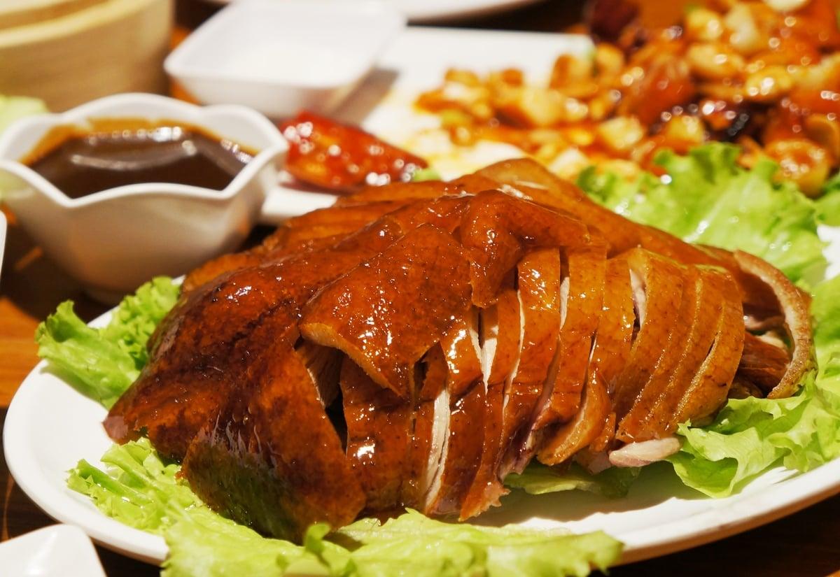 Đĩa thịt vịt quay Bắc Kinh vàng giòn đã thái thành miếng được lót 1 lớp rau sống xanh và cạnh có bát nước chấm