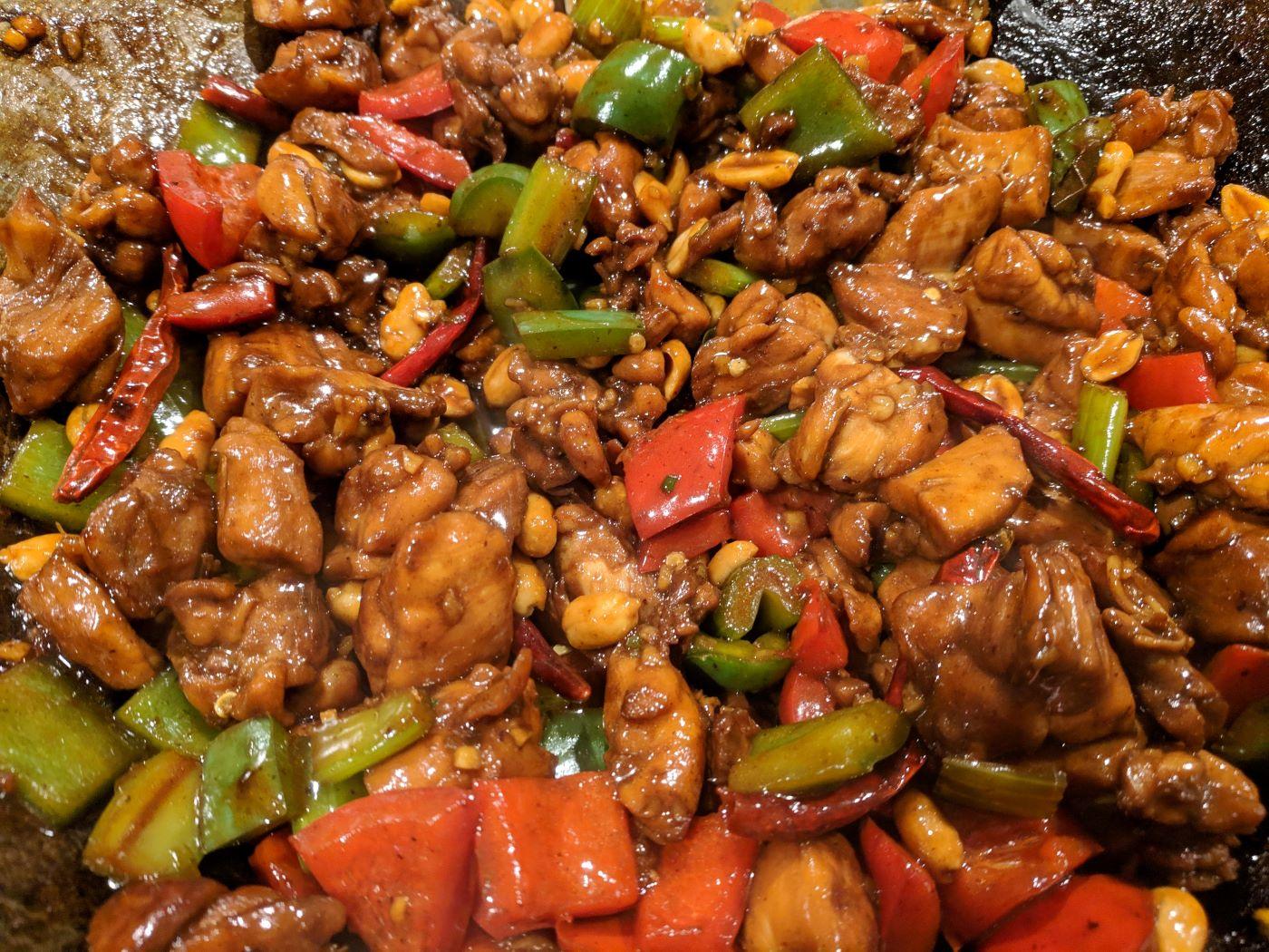 Món gà xào cay Kung Pao miếng gà thái nhỏ cùng các loại rau củ và ớt, màu đỏ vàng sánh ngon