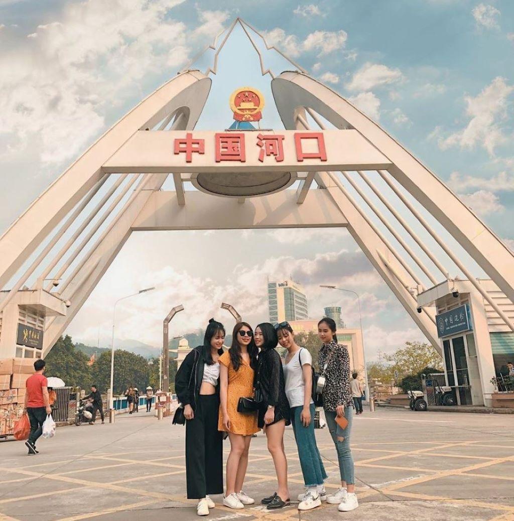 5 bạn nữ đứng check in trước cửa khẩu Hà Khẩu, cổng cửa khẩu mái vòng có in dòng chữ đỏ