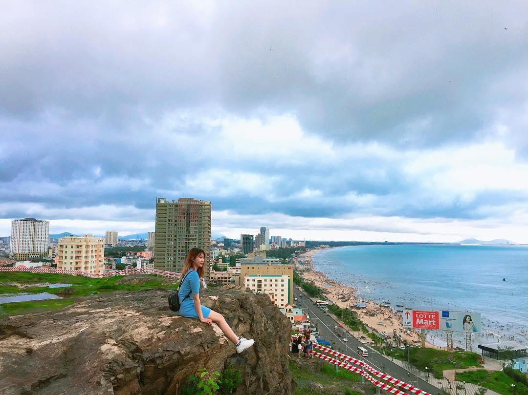 Bạn nữ ngồi chụp ảnh trên đồi Con Heo vào mùa khô trơ trụi cây, view nhìn thành phố biển