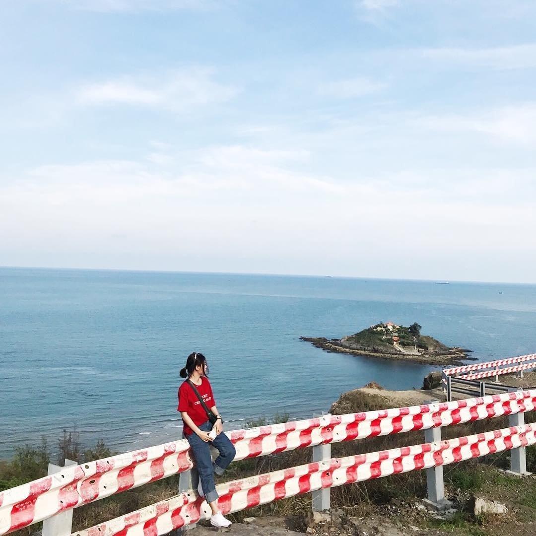 Một bạn nữ mặc áo phông đỏ, quần jeans, giày thể thao đơn giản nhưng năng động tại Đồi Con Heo