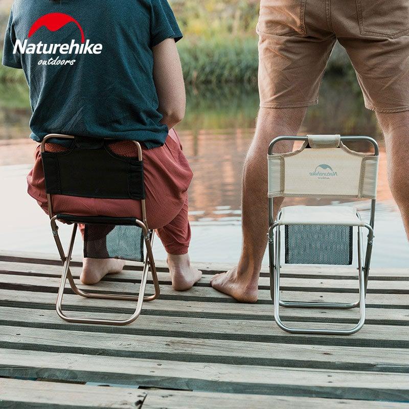 2 người ngồi ghế xếp có tựa lưng khi đi câu cá