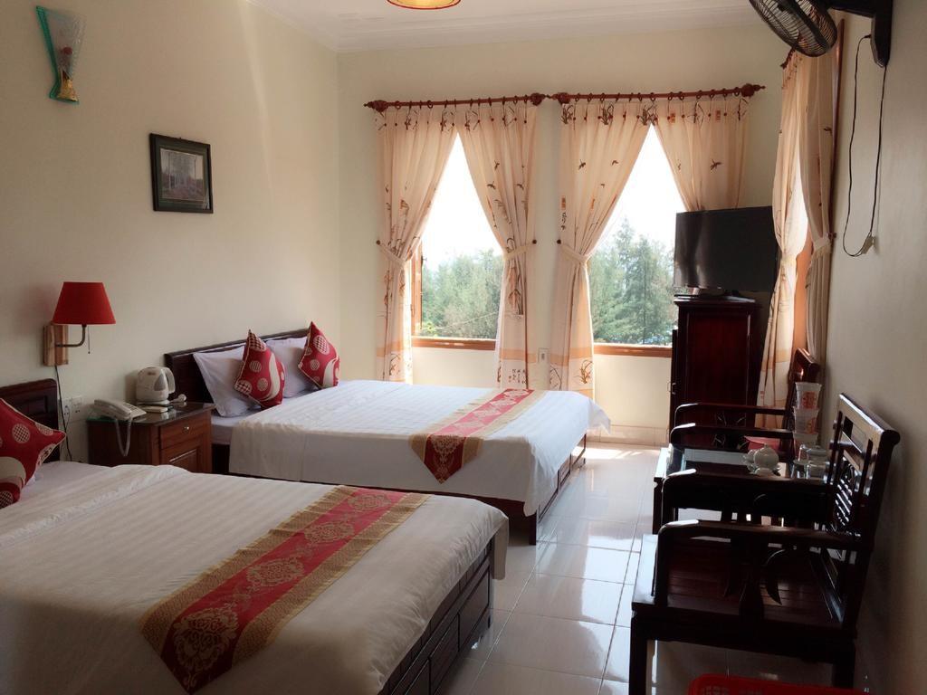 Nội thất phòng ngủ khách sạn Ban Mai đầy đủ tiện nghi có ghế, tủ, 2 giường, view cửa sổ xanh mát