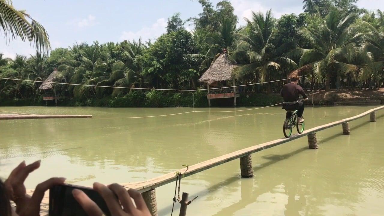 Bạn du khách mặc quần áo bà ba đang đi xe đạp qua cầu khỉ bắc qua sông ở khu du lịch Lan Vương Bến Tre