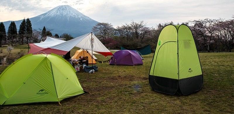 Lều thay đồ màu xanh lá được dựng bên cạnh các lều cắm trại dã ngoại khác trên khu đất trống