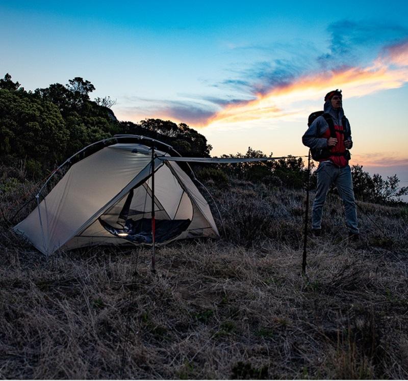 Người đàn ônh đững bên lều trắng được dựng trên địa hình cỏ, đất
