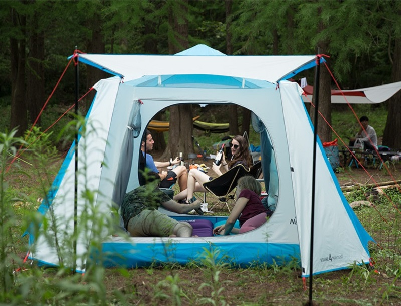 2 người trong lều trò chuyện vui vẻ cùng 2 người ngồi ghế bên ngoài lều khi cắm trại trong rừng