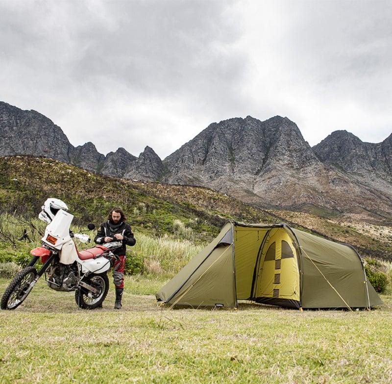 Người đàn ông cùng xe máy đứng cạnh lều trên địa hình dưới chân đồi núi đầy cỏ đất bằng phẳng