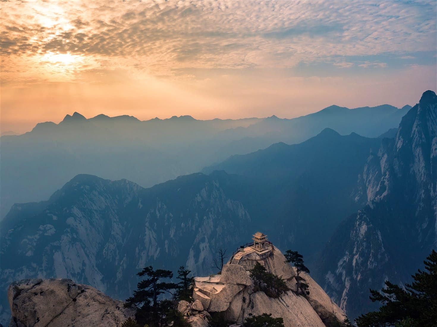 Trên đỉnh núi Liên Hoa Sơn vách đá cao chót vót mờ sương nhìn ra những dãy núi xa xa và bầu trời vàng cam
