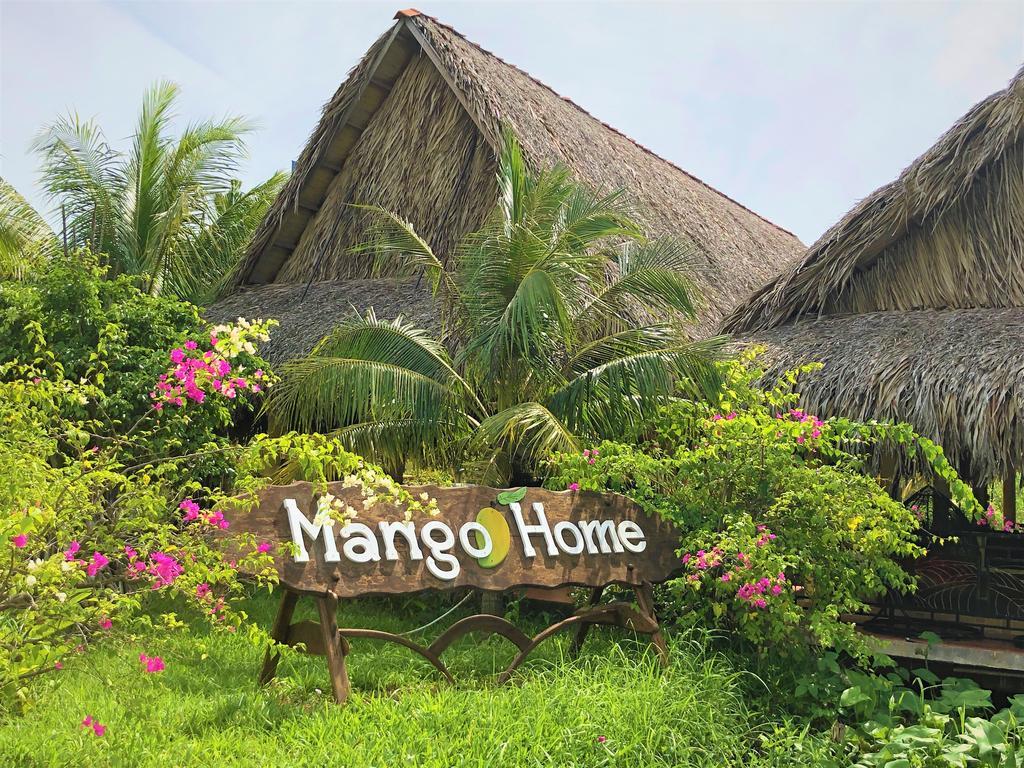 Biển gỗ Mango Home cắm trong vườn hoa, cây xanh bên cạnh là những căn nhà chòi lợp bằng lá dừa