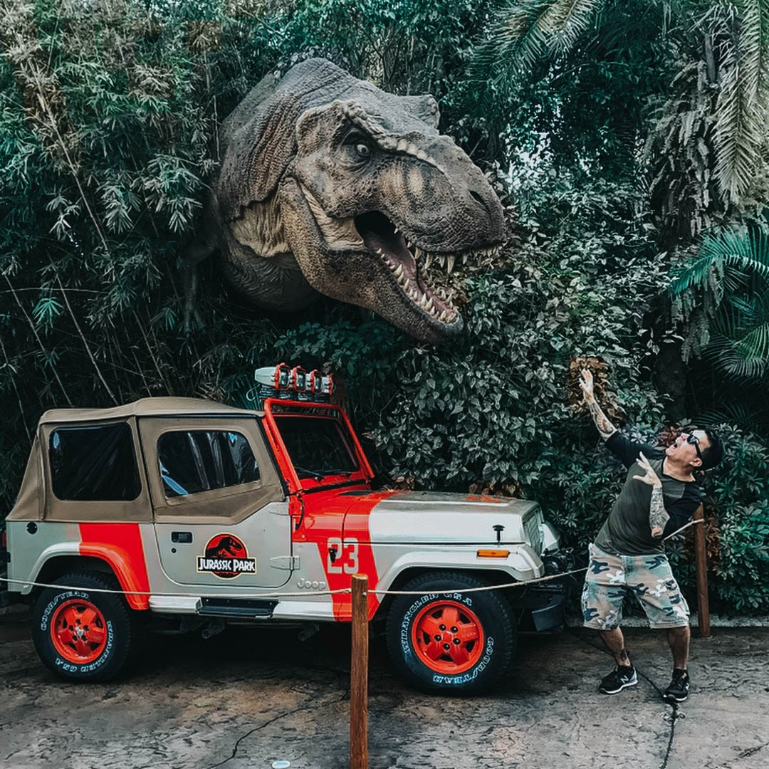 Mô hình khủng long 3D giữa bụi cây xanh và du khách nam đang tạo dáng chụp ảnh cùng