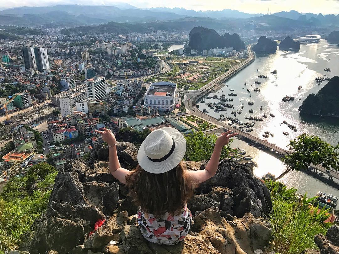 Một bạn nữ đang ngồi ở đỉnh núi Bài Thơ ngắm toàn cảnh Hạ Long