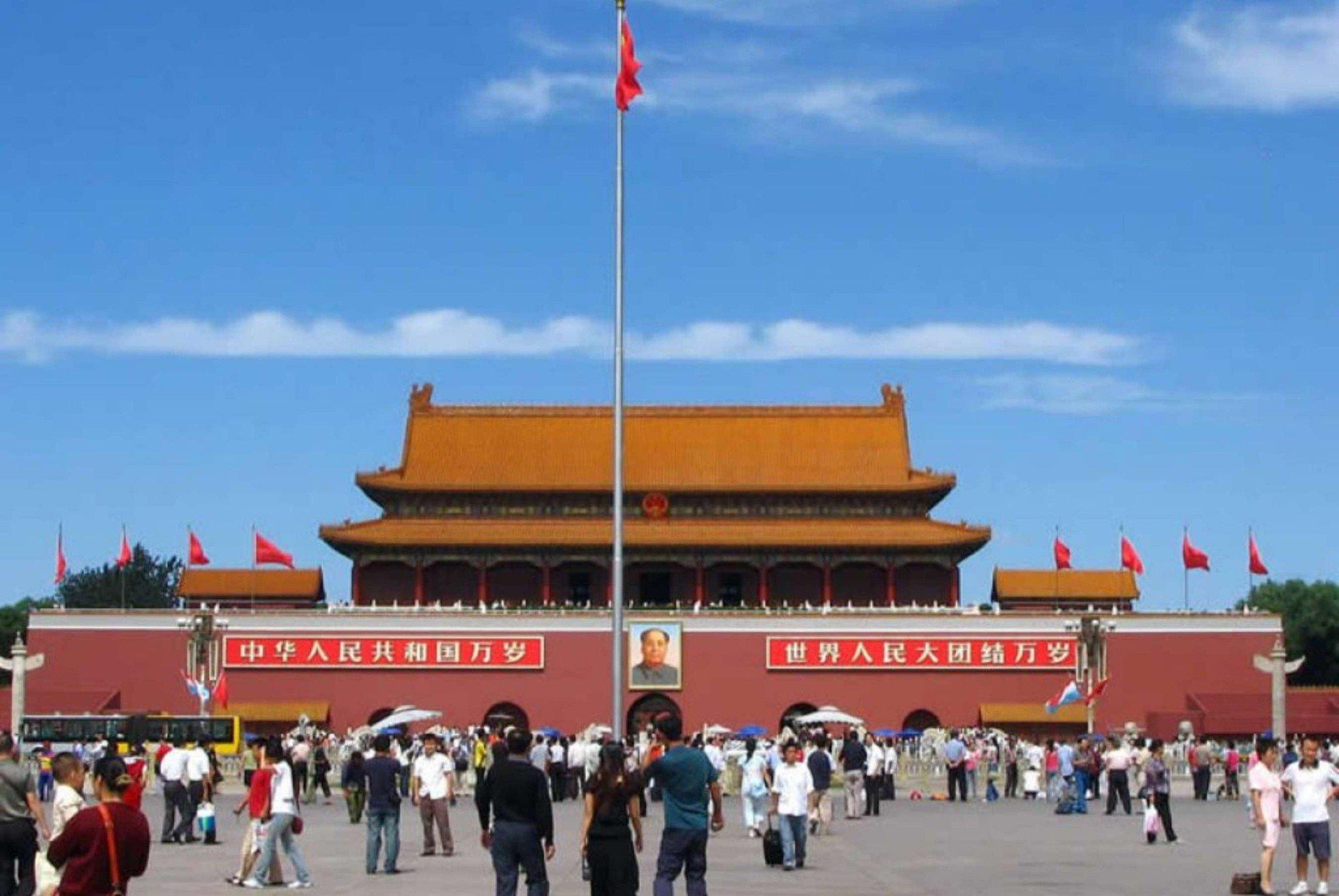 Trước quảng trường Thiên An Môn rộng lớn có nhiều người, cột cờ cao và hình ảnh Mao Trạch Đông