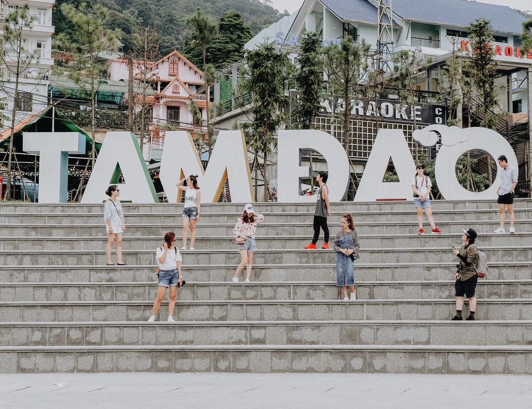 Nhóm bạn nữ đang đứng tạo dáng chụp ảnh trên bậc thang cùng hàng chữ trắng Tam Đảo ở quảng trường tam đảo