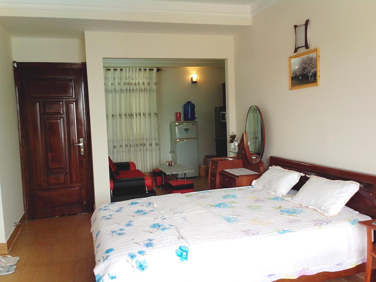 Phòng nghỉ của Sakura Hotel đầy đủ tiện nghi có bàn ghế, tủ lạnh, giường đệm trắng, sạch sẽ