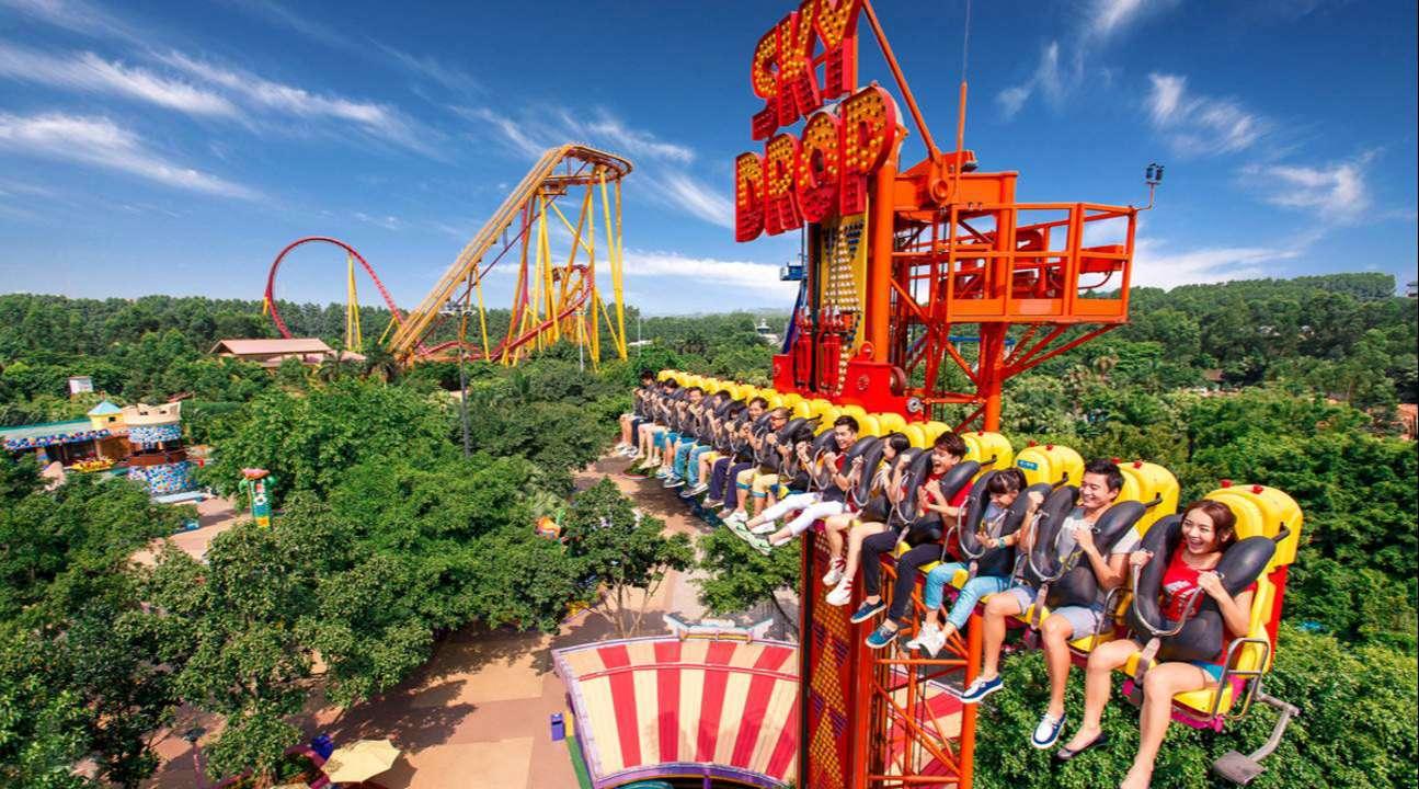 Rất nhiều du khách đang chơi trò tàu lượn siêu tốc trên không trung, nhìn xuống cảnh khu vui chơi lẫn vào tán cây xanh