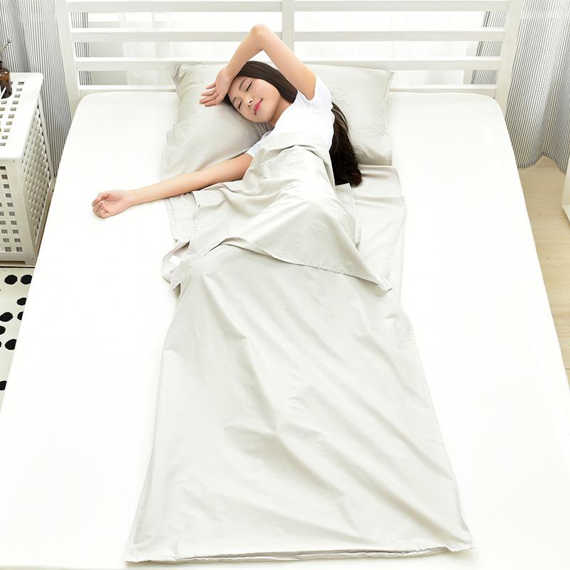Bạn nữ nằm ngủ thoải mái trong túi ngủ màu trắng trải trên giường