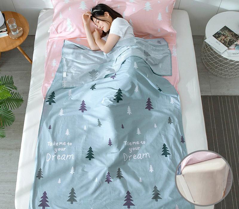 Bạn nữ nằm ngủ thoải mái trong chiếc túi ngủ màu xanh hoạ tiết cây thông nhỏ bé