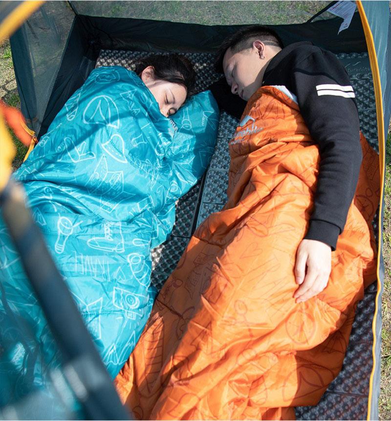 Bạn nữ và bạn nam mỗi người 1 túi ngủ màu cam, màu xanh nằm ngủ ngon trong lều