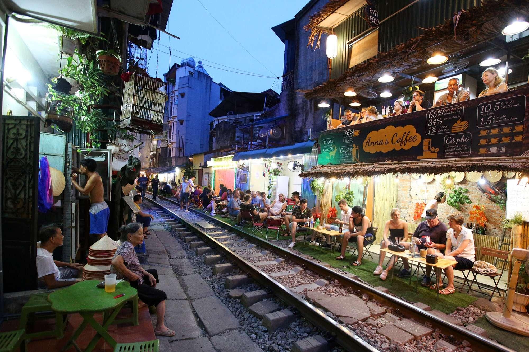Rất nhiều người đang ngồi trò chuyện vui vẻ, uống nước ở hàng quán bên cạnh đường tàu