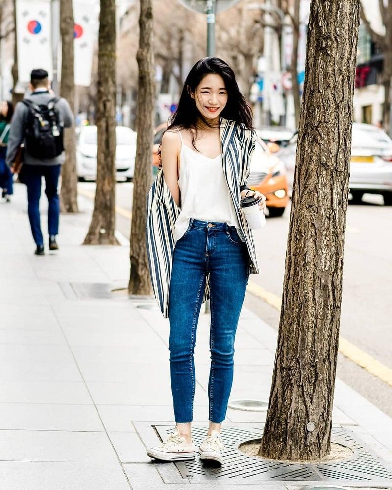 Áo sơ mi sọc dọc khoác ngoài áo hai dây kết hợp cùng quần jean lưng cao trẻ trung.