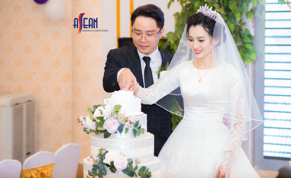 Cảnh cắt bánh cưới của cô dâu chú rể tại lễ thành hôn