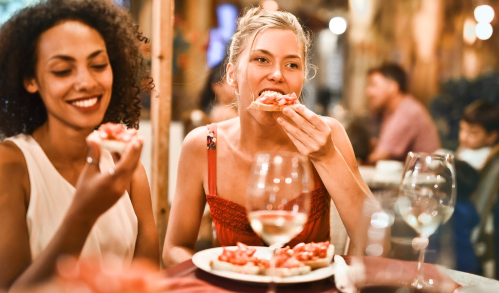 2 woman eating at restaurant with wine